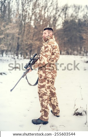professional hunter looking for prey during winter season. War, hunting or protection concept with young sniper - stock photo