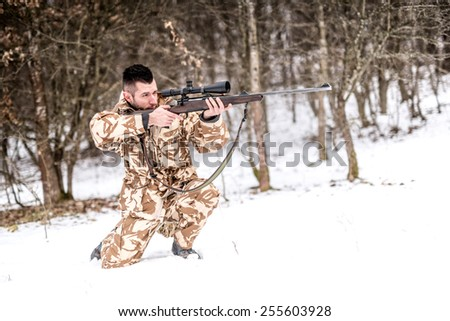 Professional hunter with sniper rifle aiming and shooting during winter  - stock photo