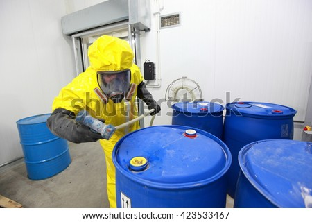 Professional in uniform working with  barrels with chemicals
