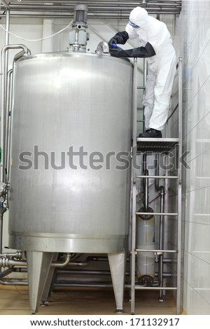 professional in white protective uniform,mask,goggles,gloves opening  large industrial process  tank in factory
