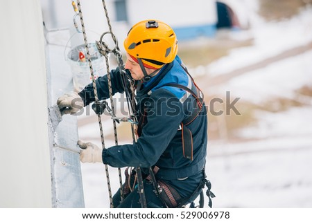 Professional industrial climber works at height. Risky extreme job.