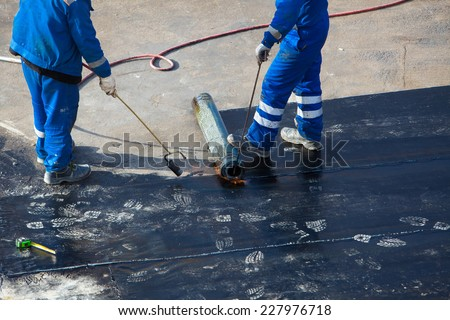 Professional installation of waterproofing on the concrete foundation. Two worker at construction site. - stock photo