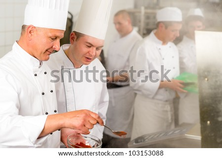 Professional kitchen chef cook add spice paprika prepare food meals - stock photo
