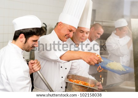 Professional kitchen happy chef prepare food meal international cuisine - stock photo