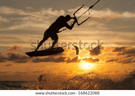 professional kiter makes the difficult trick on a beautiful background of spray and beautiful sunset of Mauritius - stock photo