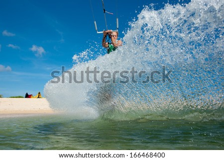 professional kiter makes the difficult trick on a beautiful background of spray and beautiful white sand of Mauritius - stock photo