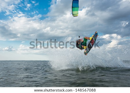 professional kiter makes the difficult trick on a beautiful background of spray and clouds - stock photo