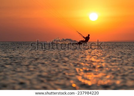 professional kiter makes the difficult trick on a beautiful background of spray and colourful sunset of Black sea - stock photo