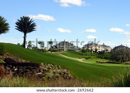 professional landscaping at a golf resort with mansions on the hill - stock photo