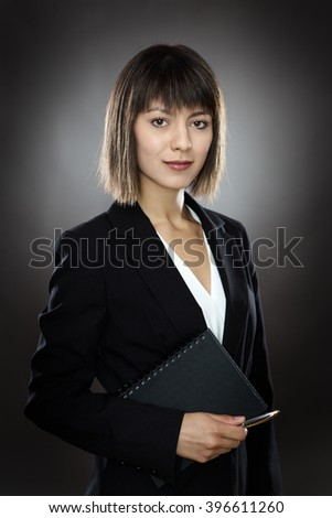 professional looking business woman holding a notebook and pen