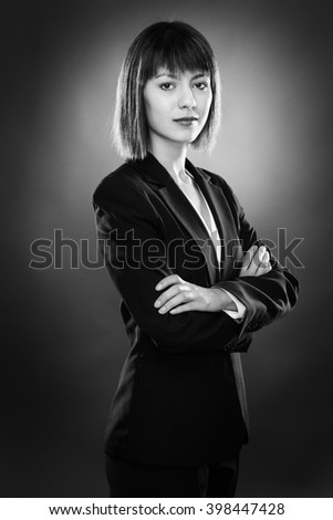 professional looking business woman looking at camera low key lighting shot on a gray background