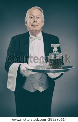 Professional Looking Senior Male Butler Wearing Tuxedo and Carrying Tray with Liquor Bottle and Two Crystal Cordial Glasses - stock photo