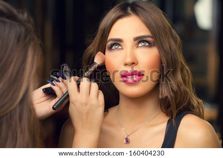 Professional make-up artist applying makeup to a beautiful model - stock photo