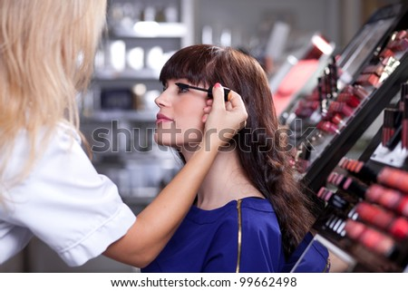 Professional make up artist applying mascara in a beauty store - stock photo