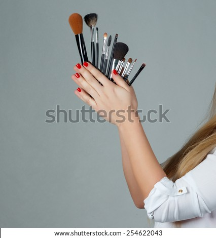 Professional make-up brush cosmetic in female hand beautician. gray background