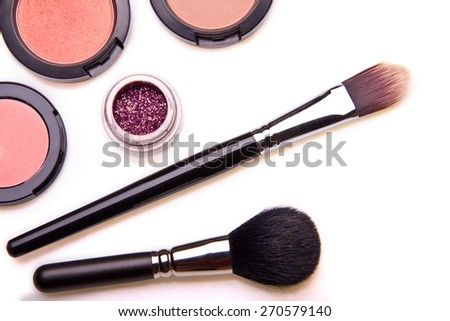 Professional make up set: make-up brushes and shadows - partly isolated with shadows on white background. Overhead view. - stock photo