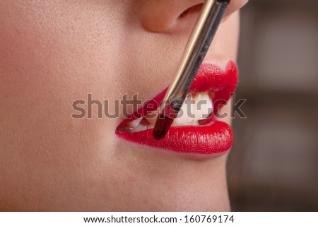 Professional makeup artist applying lipstick
