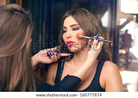 Professional makeup artist applying make up on a beautiful young model's face - stock photo