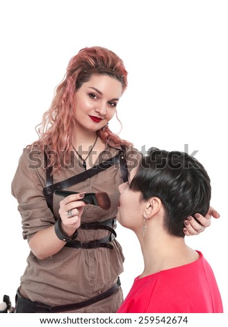 Professional makeup artist making makeup to a model isolated on white background - stock photo