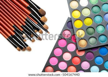 Professional makeup brushes and eyeshadow palette on white background