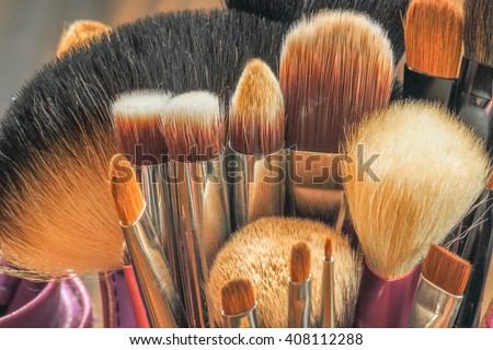 Professional makeup brushes in tube. Dirty makeup tools. - stock photo
