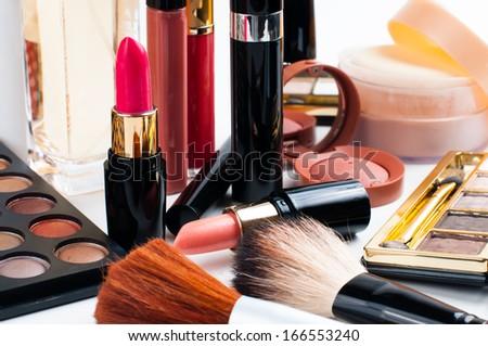 Professional makeup set: eyeshadow palette, lipstick, mascara, blush, powder, make-up brushes and perfume, many cosmetics closeup. - stock photo