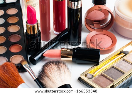 Professional makeup set: eyeshadow palette, lipstick, mascara, blush, powder, make-up brushes and perfume, many cosmetics closeup. - stock photo
