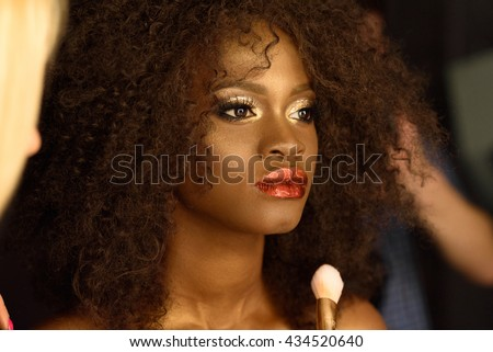 Professional makeup with a beautiful young black woman having touches applied to her make up by beautician - stock photo