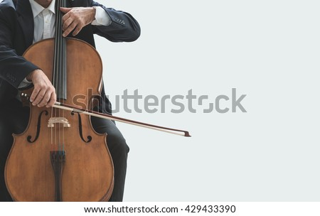 Professional male cellist playing his cello, classical music solo performance - stock photo
