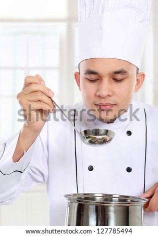 professional male chef smell his cooking in the kitchen - stock photo