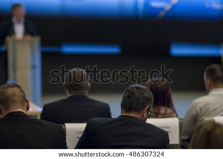 Professional Male Host Speaking in Front of the Audience During Business Conference. Presentation on Dark Screen. Horizontal Image Composition