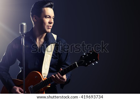Professional male musician  plays and sing in the style of the sixties. Rock'n'roll, jazz man. Beat generation. Nostalgia. - stock photo