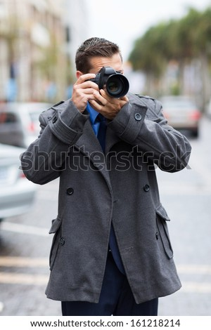 professional male photographer taking street photos in the city in a raining day - stock photo
