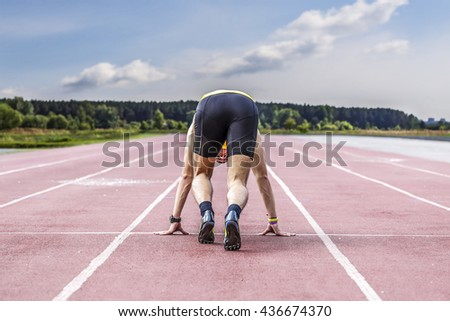Professional male runner taking ready to start position