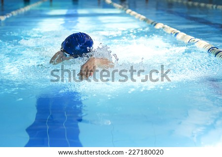 Professional male swimmer swimming in the pool - stock photo