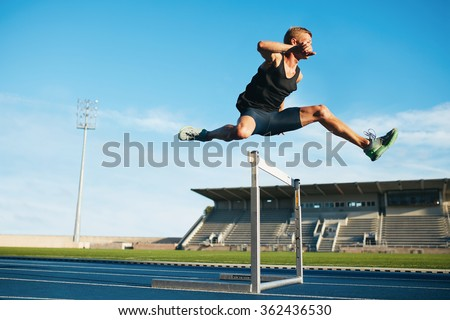 Professional male track and field athlete during obstacle race. Young athlete jumping over a hurdle during training on racetrack in athletics stadium. - stock photo