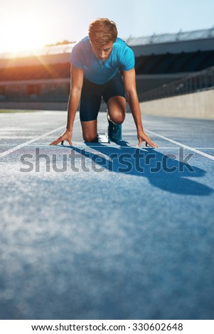 Professional male track athlete in set position on sprinting blocks of an athletics running track in stadium. - stock photo