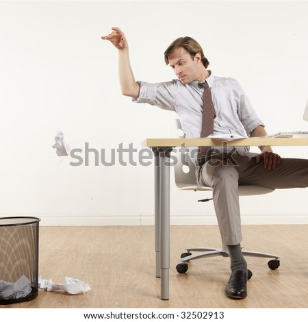 professional man sitting at desk throwing papers in wastebasket - stock photo