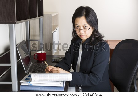 Professional Mature Asian woman with glasses down while working on income taxes with tax form booklet, calculator, coffee cup and computer on desk - stock photo