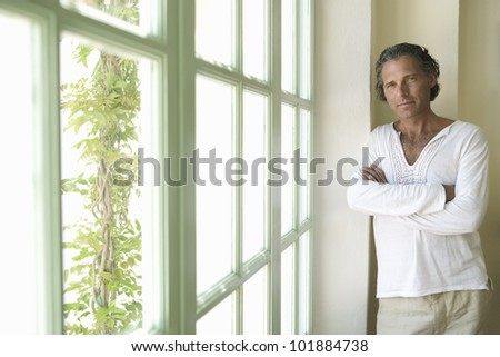 Professional mature man at home leaning by a large window and smiling at camera. - stock photo