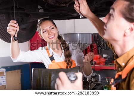 Professional mechanics crew repairing a broken car at auto service center  - stock photo