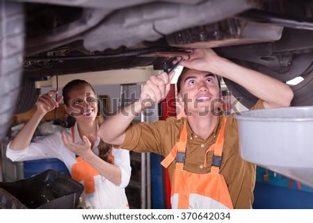 Professional mechanics repairing a broken car at auto service center  - stock photo