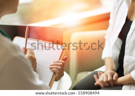 Professional medical doctor in white uniform gown coat interview counseling female patient: Physician writing on patient chart while consultation: Hospital/ clinic healthcare professionalism concept