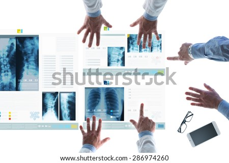 Professional medical team examining patient's medical records and x-ray on touch screen slides and pointing - stock photo