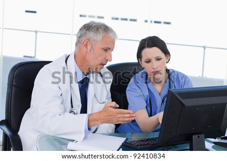 Professional medical team working with a computer in an office - stock photo