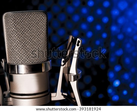 Professional microphone silver on black and blue background