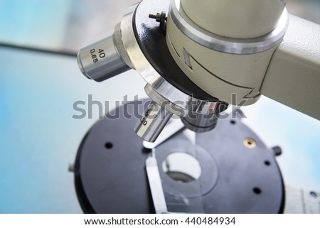 Professional microscope close-up with chemist scientific researcher hands using microscope in the laboratory interior. - stock photo