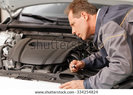 Professional mid aged technician is adjusting the car. He is standing and holding a spanner. The man is looking at the engine with seriousness