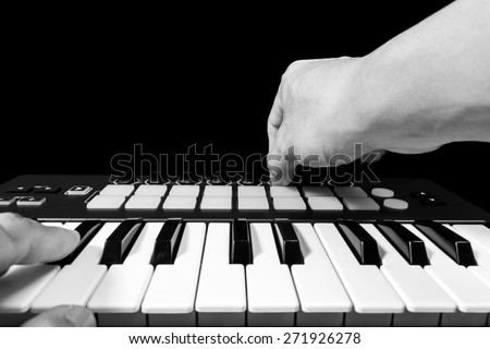 professional musician hand playing on studio keyboard synthesizer, focus to right thumb on knob + B&W isolated on black for dance , groove, remix, dubstep music background concept - stock photo