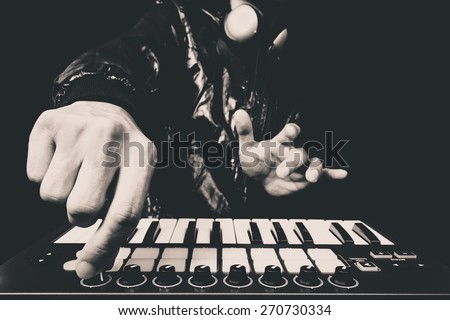 professional musician or DJ hand on studio keyboard synthesizer, B&W isolated on black for dance , groove, remix, underground music background concept - stock photo